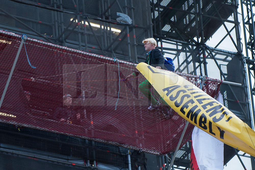 © Licensed to London News Pictures. 18/10/2019. LONDON, UK.  A construction worker in conversation with a climate activist (green tights) from Extinction Rebellion who has scaled the construction scaffolding of the Queen Elizabeth Tower in Westminster.  Parliament Square and the surrounding area has been brought to a standstill as police and emergency services assess the situation.  Photo credit: Stephen Chung/LNP