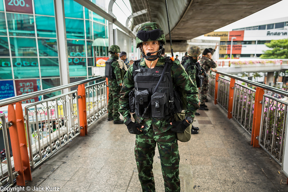 29 MAY 2014 - BANGKOK, THAILAND: Thai soldiers patrol the skywalk at the Victory Monument BTS Skytrain station. After a series of protests around Victory Monument earlier in the week, the Thai army Thursday shut down vehicle access to the area, one of the main intersections in Bangkok, and kept people out of the area. Thousands of soldiers surrounded the Monument and effectively locked the area down. There were no protests at Victory Monument for the first time in the week since the coup deposed the elected civilian government.   PHOTO BY JACK KURTZ