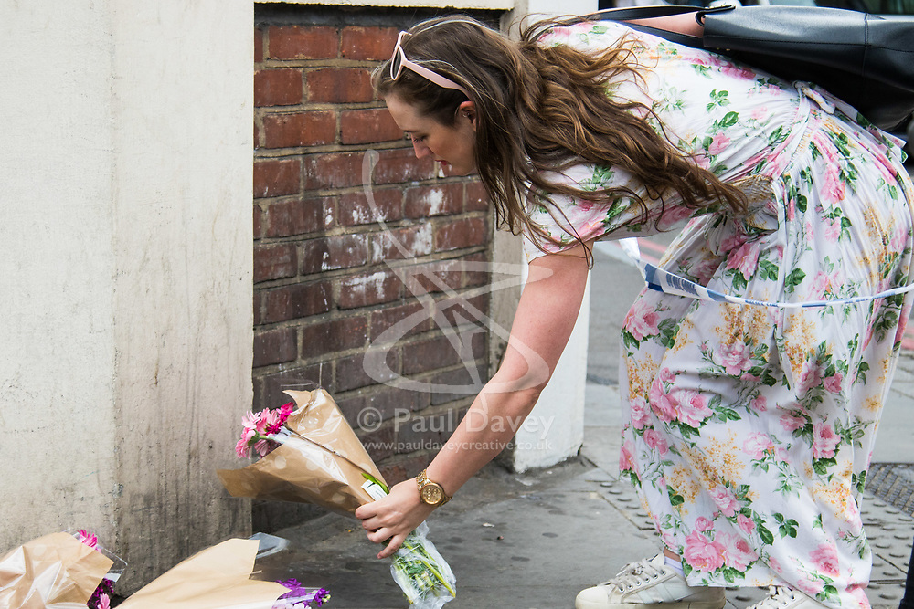 London, June 4th 2017. A woman places flowers at Borough High Street during a massive policing operation in the aftermath of the terror attack on London Bridge and Borough Market on the night of June 3rd which left seven people dead and dozens injured