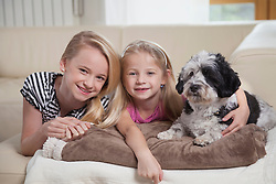 Two sisters with dog in a living room, Bavaria, Germany