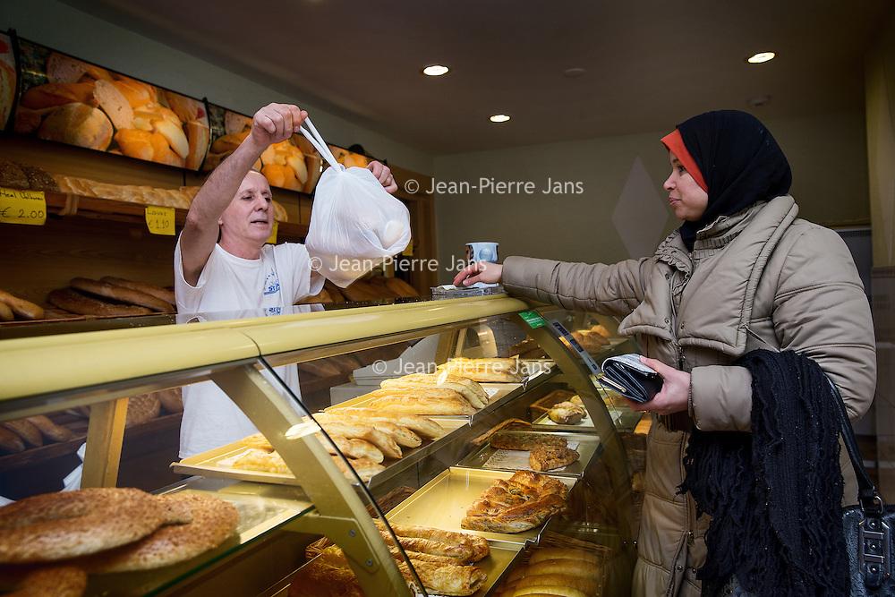 Nederland, Amsterdam, 2 februari 2016.<br /> Mona Ghadir uit de Transvaalbuurt doet boodschappen in de Pretoriastraat om falaffel te maken.<br /> Op de foto: Mona haalt brood bij de Turkse warme bakker Safak Firini in de Pretoriastraat.<br /> <br /> Reportage of egyptian Mona Ghadir living in Amsterdam. Today she shops for ingredients and prepares typical egyptian dishes. <br /> <br /> Foto: Jean-Pierre Jans