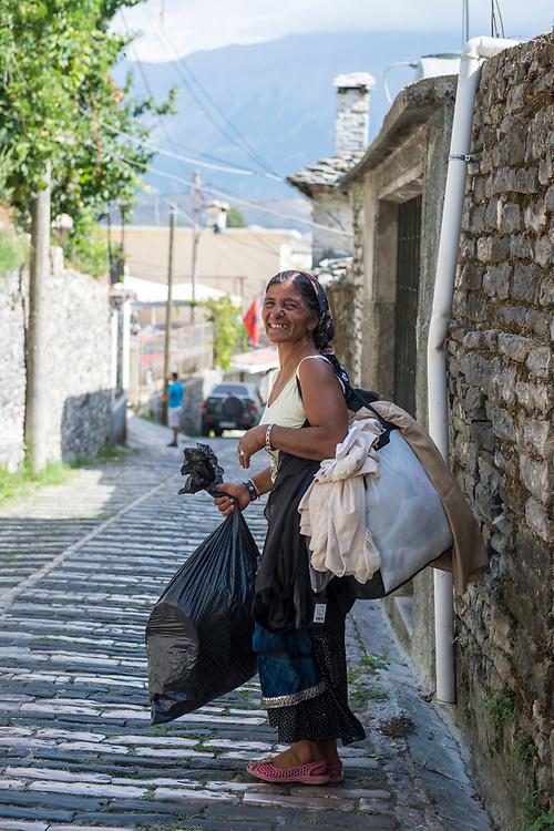 Gjirokastër, Albania - September 11, 2013: A woman turns and smiles at a photographer in Gjirokastër, Albania.