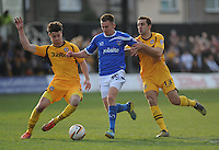 Portsmouth's Jed Wallace is tackled by Newport County's Andrew Hughes<br /> <br /> Photo by Ashley Crowden/CameraSport<br /> <br /> Football - The Football League Sky Bet League Two - Newport County AFC v Portsmouth - Saturday 29th March 2014 - Rodney Parade - Newport<br /> <br /> © CameraSport - 43 Linden Ave. Countesthorpe. Leicester. England. LE8 5PG - Tel: +44 (0) 116 277 4147 - admin@camerasport.com - www.camerasport.com