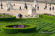 France, Paris, Couple sitting in Truileries Garden with flowers and greenery