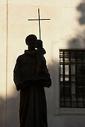 The silhouette of a religious statue outside of a church in the Alfama district of Lisbon, Portugal