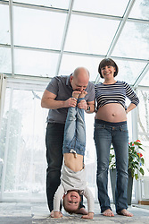 Father holding son upside down with portrait of pregnant mother