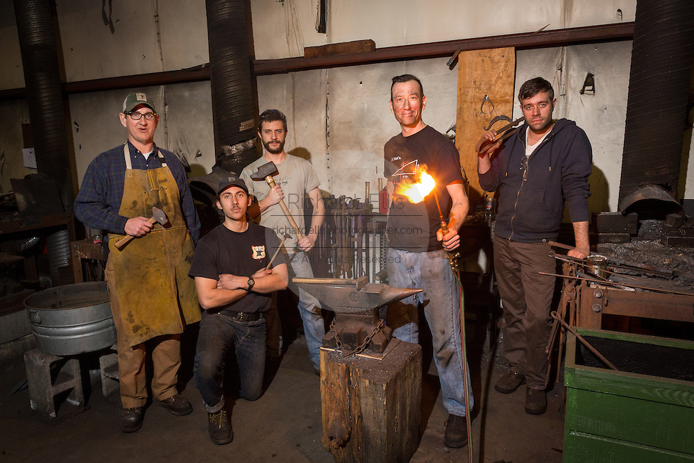 Blacksmiths from the College of the Building Arts pose for a portrait in a metal working shop in Charleston, SC