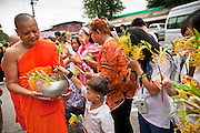 "15 JULY 2011 - PHRA PHUTTHABAT, SARABURI, THAILAND:    People present flowers and candles to monks during the Tak Bat Dok Mai at Wat Phra Phutthabat in Saraburi province of Thailand, Friday, July 15. Wat Phra Phutthabat is Phra Phutthabat, Saraburi, Thailand, is famous for the way it marks the beginning of Vassa, the three-month annual retreat observed by Theravada monks and nuns. The temple is highly revered in Thailand because it houses a footstep of the Buddha. On the first day of Vassa (or Buddhist Lent) people come to the temple to ""make merit"" and present the monks there with dancing lady ginger flowers, which only bloom in the weeks leading up Vassa. They also present monks with candles and wash their feet. During Vassa, monks and nuns remain inside monasteries and temple grounds, devoting their time to intensive meditation and study. Laypeople support the monastic sangha by bringing food, candles and other offerings to temples. Laypeople also often observe Vassa by giving up something, such as smoking or eating meat. For this reason, westerners sometimes call Vassa the ""Buddhist Lent."" The tradition of Vassa began during the life of the Buddha. Most of the time, the first Buddhist monks who followed the Buddha did not stay in one place, but walked from village to village to teach. They begged for their food and often slept outdoors, sheltered only by trees. But during India's summer rainy season living as homeless ascetics became difficult. So, groups of monks would find a place to stay together until the rain stopped, forming a temporary community. Wealthy laypeople sometimes sheltered monks on their estates. Eventually a few of these patrons built permanent houses for monks, which amounted to an early form of monastery.  PHOTO BY JACK KURTZ"