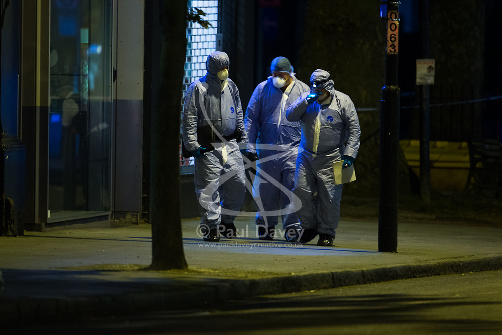 Forensics investigators work at the scene following a fatal stabbing of a man in broad daylight at around 6.30pm on Upper Street in Islington, North London. London, May 21 2018.