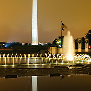 Night shot of the Washington Monument with the fountains of the World War II Memorial in the foreground.