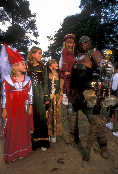Stock photo of a large man with a sword posing with young children at the Texas Renaissance Festival in Plantersville Texas