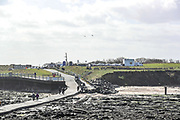 Visitors are seen walking away from the Lighthouse tower of St. Mary's Island after they visit and observed Seals sunbathing on Wednesday, March 17, 2021 - which is a small sandstone island near the seaside resort of Whitley Bay in the north of England. It is a Local Nature Reserve. Located in the seaside town on the northeast coast of England, it is administered as part of the borough of North Tyneside in Tyne and Wear. (Photo/ Vudi Xhymshiti)