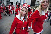London, UK. Sunday 9th December 2012. A flash mob of Santas descends play to camera. Christmas celebrated here with the annual Santa Pub Crawl party visiting the famous pubs & sights of London with everyone decked out in jolly red Santa suits. Organised by Fanatics, an Australian sports and party company.