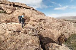 Sarah Hepola carrying bouldering pads to climbing site, Hueco Tanks State Park & Historic Site, El Paso, Texas. USA.