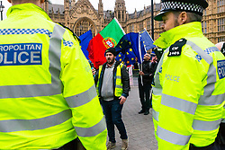 Pro-Brexit campaigner James Goddard, centre, in his 'gilet juane' is watched by police as he once again visits and attempts to disrupt Steve Bray's SODEM anti-Brexit protest the day after he was seen harassing former cabinet minister Anna Soubry. Westminster, London, December 20 2018.