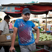 A young man whose job it is to haul produce by wheelbarrow in a market in Jenin, the West Bank. Unemployment for young Palestinians over 20% and the starting wage is around $20 a day.