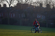 With the rears of homes in the background, a man teaches a young boy to ride a bike on a grassy park slope, on 5th January 2017, in Ruskin Park, London borough of Lambeth, England.