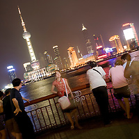 Asia, China, Shanghai, Chinese tourists pose for snapshots along The Bund, overlooking Oriental TV Tower and Pudong skyline along Huangpu River at night.