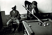 Youths playing and sitting, in pool club room. Photo by Richard Saunders 1983