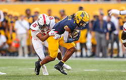 Oct 2, 2021; Morgantown, West Virginia, USA; West Virginia Mountaineers wide receiver Winston Wright Jr. (1) makes a catch and is tackled by Texas Tech Red Raiders defensive back Dadrion Taylor-Demerson (25) during the fourth quarter at Mountaineer Field at Milan Puskar Stadium. Mandatory Credit: Ben Queen-USA TODAY Sports