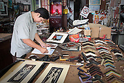 A picture framer at work at a frame shop in Georgetown on Penang in Malaysia.