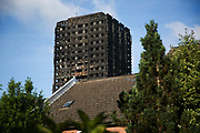 View of Grenfell Tower behind green tress June 16th 2017, London, United Kingdom. Grenfell Tower burned out after a catastophic fire killing more than 58 people. The tower caught fire early Wednesday morning and final casualty figueres may end up to be many more with police not expecting to be able to find and recover all bodies and to find all missing people. No fire sprinkler in place and cheap cladding made with plastic is so far blamed for the ferocious fire.