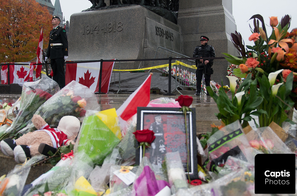An honour guard stands behind flowers and a photo of Cpl. Nathan Cirillo at the National War Memorial. An Ottawa police tactical officer watches over nearby. October 25, 2014