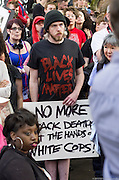 A demonstrator at at 2015 May Day rally in Portland, Oregon holds a sign protesting black deaths while wearing a t-shirt that says Black Lives Matter