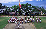 Children stand to attention as the Philippine flag is raised and they sing  the National Anthem at Francisco Benitez primary school overlloking Gumacas bay, the Sierra Madre visible in the background, Busok Busok village, Philippines