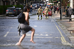 © Licensed to London News Pictures. 24/06/2021. London, UK. Members of the public take off their shoes to wade through water in St John's Wood, North London, where a burst pipe has has cause flooding across a number of streets in the area. Photo credit: Ben Cawthra/LNP