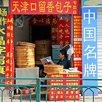 Asia, China, Chongqing. A shopkeeper reads a newspaper.