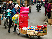 "22 DECEMBER 2017 - HANOI, VIETNAM:  A woman pushes her cart of dry goods that she sells on the streets in the old quarter of Hanoi. The old quarter is the heart of Hanoi, with narrow streets and lots of small shops but it's being ""gentrified"" because of tourism and some of the shops are being turned into hotels and cafes for tourists and wealthy Vietnamese.   PHOTO BY JACK KURTZ"