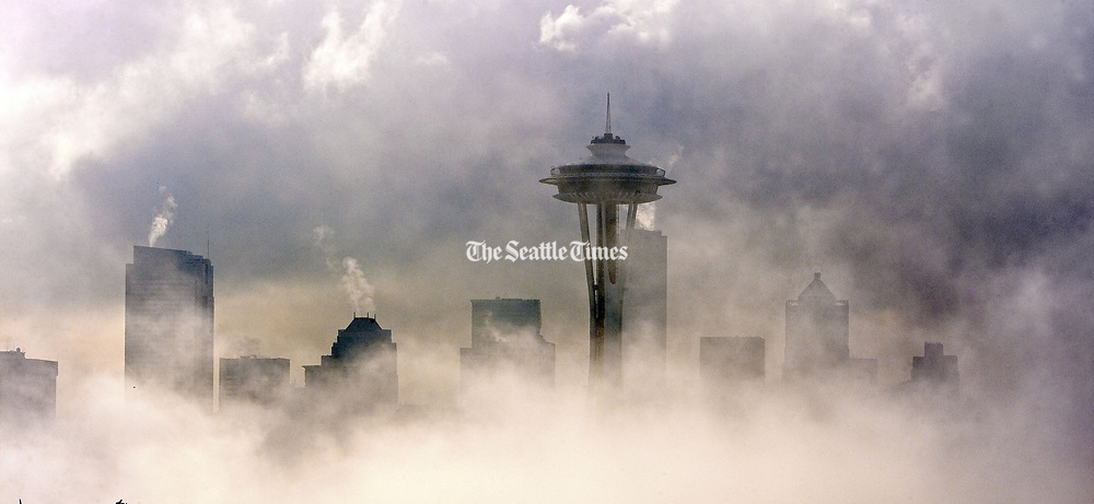 The Space Needle and downtown Seattle  begin to emerge from a fog blanket in this view from Kerry Park on the south side of Queen Anne Hill. (Mike Siegel / The Seattle Times, 2009)