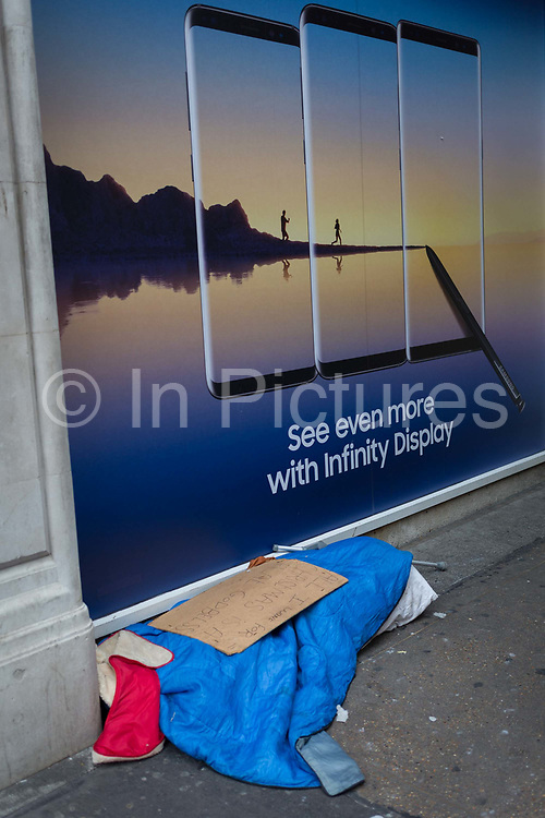 The possessions of a homeless person beneath an aspirational ad for Samsungs Infinity Display and a paradise lifestyle, on 22nd November 2017, in London England.