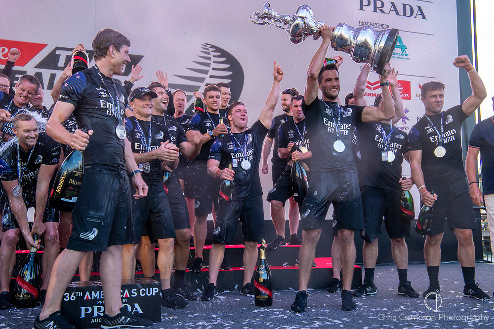 Blair Tuke holds the Cup.Emirates Team New Zealand celebrate on stage after being presented with the Americas Cup on stage after beating Luna Rossa Prada Pirelli Team 7 - 3. Glen Ashby pours for Peter Burling.  Wednesday the 17th of March 2021. Copyright photo: Chris Cameron