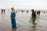 Two men dressed as Elsa and Anna from Frozen. Participants dressed up for Folkestone Lions Club Boxing Day Dip.  An annual fancy dress fundraising event, where all sorts of amusing costumes and characters enter the cold sea of the English Channel at Sunny Sands, Folkestone. UK.