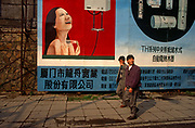 Chinese citizens walk beneath a billboard for shower and bathroom equipment in the new megacity of Shenzhen, China. A happy-looking woman showers herself with a big smile on her face and Chinese characters give more details below. Two men walk past looking the other way.