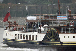 © Licensed to London News Pictures. 11/10/2013. Passengers hid from the rain as the he famous and much loved paddle steamer Waverley passed maritime Greenwich today as she nears the end of her season on the Thames. Credit : Rob Powell/LNP