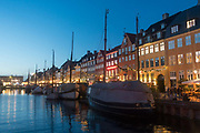 Dusk at Nyhavn on the 18th November 2017 in Copenhagen, Denmark. Nyhavn is a 17th-century waterfront, canal and entertainment district in Copenhagen. Stretching from Kongens Nytorv to the harbour front just south of the Royal Playhouse, it is lined by brightly coloured 17th and early 18th century townhouses and bars, cafes and restaurants. The canal harbours many historical wooden ships.