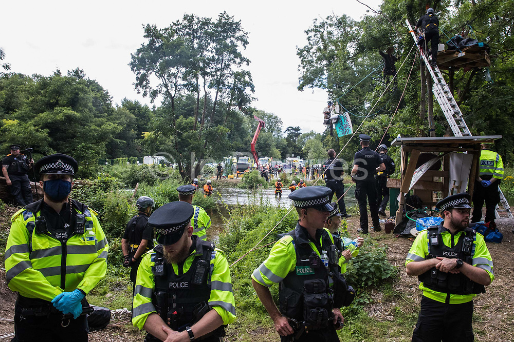 Thames Valley police officers take part in a large policing operation in Denham Country Park to ensure that environmental activists from HS2 Rebellion did not prevent removal of an ancient alder tree alongside the river Colne for the HS2 high-speed rail link on 24th July 2020 in Denham, United Kingdom. Officers from the Metropolitan Police, Thames Valley Police, City of London Police and Hampshire Police attended as well as the National Eviction Team.