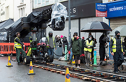 © Licensed to London News Pictures; 21/02/2021; Bristol, UK. Filming takes place in East Street in Bedminster for Extinction, a Sky Original eight-part series produced by Urban Myth Productions in association with Sky Studios. This scene is set in the latter part of the 20th century with period cars and some generic shop fronts. The main character George is played by Paapa Essiedu, who rose to fame following his role as Kwame in BBC drama I May Destroy You. Extinction follows the story of George as he begins to re-live time after witnessing the end of the world. Film crew are seen wearing PPE during the coronavirus pandemic, along with extras who wear masks in between takes. Photo credit: Simon Chapman/LNP.