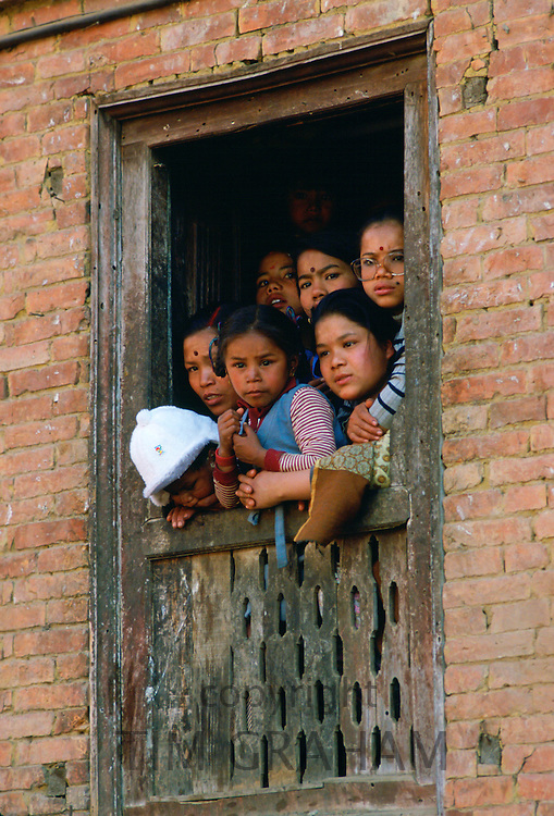 Family  at window  to watch festival in Bhaktapur, Nepal