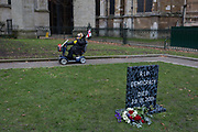 On the day that the UK Parliament once again votes on an amendment of Prime Minister Theresa Mays Brexit deal that requires another negotiation with the EU in Brussels, a far-right pro-Remain protester drives her mobility scooter past a memorial to democracy outside the House of Commons, on 29th January 2019, in Westminster, London, England.