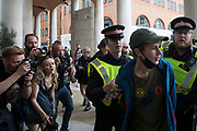 City of London Police officers detain a young activist in Paternoster Square for a search during an Extinction Rebellion Blood Money March through the City of London on 27th August 2021 in London, United Kingdom. The activist was released following the search. Extinction Rebellion were highlighting financial institutions funding fossil fuel projects, especially in the Global South, as well as law firms and institutions which facilitate them.