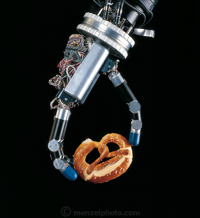Delicately handling a pretzel, the robotic hand developed at the Deutsches Zentrum für Luft und Raumfahrt (German Aerospace Center), in the countryside outside Munich, Germany, demonstrates the power of a control technique called force-feedback. To pick up an object, Max Fischer (in control room), one of the hand's developers, uses the data-glove to transmit the motion of his hand to the robot. If he moves a finger, the robot moves the corresponding finger. Early work on remote-controlled robots foundered when the machines unwittingly crushed the objects they were manipulating. From the book Robo sapiens: Evolution of a New Species, page 134.