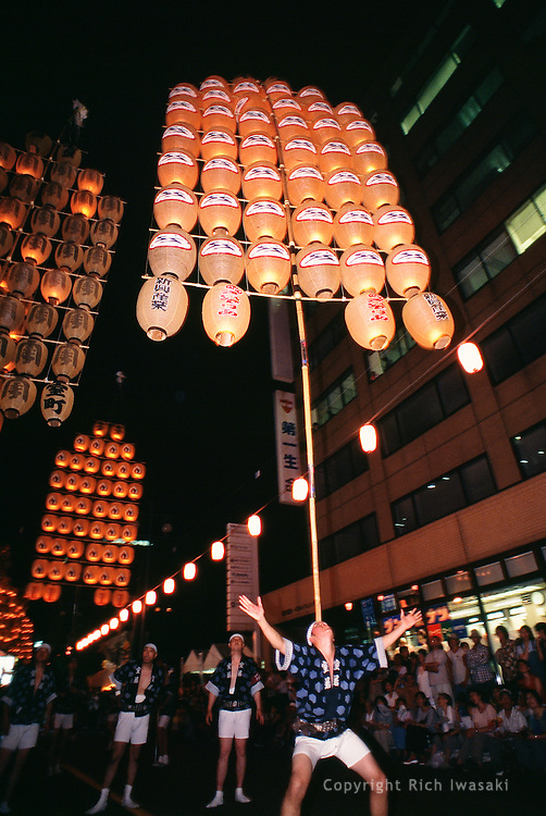 A festival performer demonstrates the art of balancing paper lanterns during the annual Kanto festival in Akita, Akita Prefecture, Japan. The 46 candle-lit lanterns on a bamboo frame weigh about 50 kg, and rise 12 meters into the air. The festival, which celebrates the prospect of an abundant rice harvest, is one of the top three summer festivals of the Tohoku region.