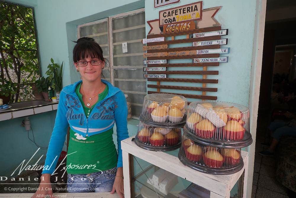 A young cuban lady sells her muffins and other baked goods on the streets of Ceinfuegos, Cuba.