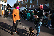 A couple with their dog are doing their vegetable shopping in Broadway Market during the second coronavirus national lockdownon on 7th of November 2020, East London, United Kingdom. The UK Government introduced a 4 week lockdown from November 5th - December 2nd to combat the coronavirus outbreak. It is the third day of the national lockdown restrictions mean that people are only allowed to meet outside, in pairs and only if keeping social distance. Only if they already live together or have formed a social bubble can they interact freely.