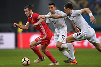 """Gareth Bale, left, of Wales national football team kicks the ball to make a pass against players of Uruguay national football team in their final match during the 2018 Gree China Cup International Football Championship in Nanning city, south China's Guangxi Zhuang Autonomous Region, 26 March 2018.<br /> <br /> Edinson Cavani's goal in the second half helped Uruguay beat Wales to claim the title of the second edition of China Cup International Football Championship here on Monday (26 March 2018). """"It was a tough match. I'm very satisfied with the result and I think that we can even get better if we didn't suffer from jet lag or injuries. I think the result was very satisfactory,"""" said Uruguay coach Oscar Tabarez. Wales were buoyed by a 6-0 victory over China while Uruguay were fresh from a 2-0 win over the Czech Republic. Uruguay almost took a dream start just 3 minutes into the game as Luis Suarez's shot on Nahitan Nandez cross smacked the upright. Uruguay were dealt a blow on 8 minutes when Jose Gimenez was injured in a challenge and was replaced by Sebastian Coates. Inter Milan's midfielder Matias Vecino of Uruguay also fired at the edge of box from a looped pass but only saw his attempt whistle past the post. Suarez squandered a golden opportunity on 32 minutes when Ashley Williams's wayward backpass sent him clear, but the Barca hitman rattled the woodwork again with goalkeeper Wayne Hennessey well beaten."""