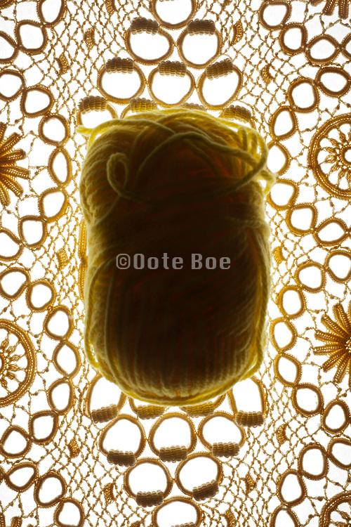 lace fabric with ball of yellow wool knitting yarn